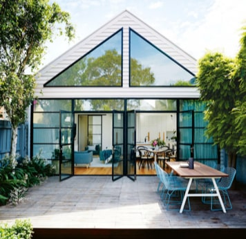 Backyard setting of Homely glass house listing with doors open